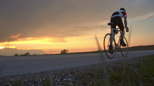 ms cyclist riding on tranquil rural road at sunset - наклон вверх стоковые видео и кадры b-roll