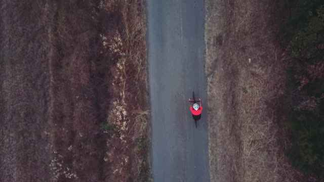 cyclist training on road bicycle outdoor: drone aerial view - percorso per bicicletta video stock e b–roll