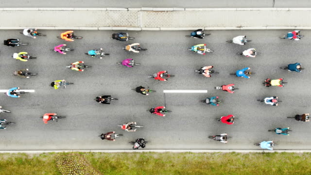 cyclists pedal and compete along broad asphalt road - vídeo