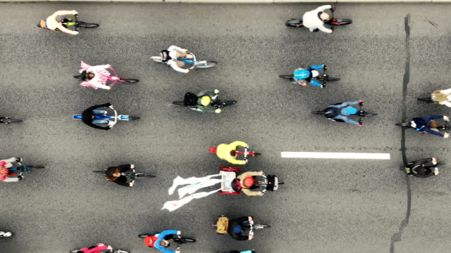Cyclists ride along the road during the bike ride, aerial view vertically down Many cyclists ride along the road during the cycle parade, aerial view vertically downwards. large group of objects stock videos & royalty-free footage