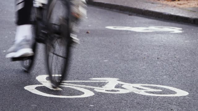Cyclists ride in a busy cycle lane in London by the Thames