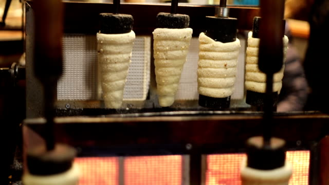 vídeos de stock e filmes b-roll de czech national winter street food called trdlo (trdelnik) is being cooked in the square of prague during christmas time - christmas cake
