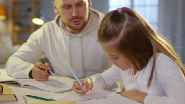 vídeos de stock, filmes e b-roll de pai e filha fazendo lição de casa à noite - salas de aula