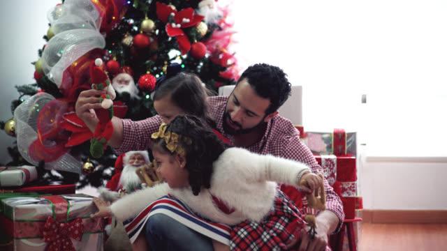 pappa och hans döttrar, i granen öppna presenter - christmas gift family bildbanksvideor och videomaterial från bakom kulisserna