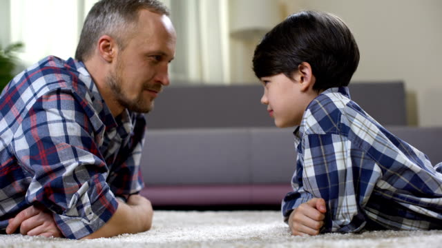 Dad and his son looking at each other and competing in force, playing game video