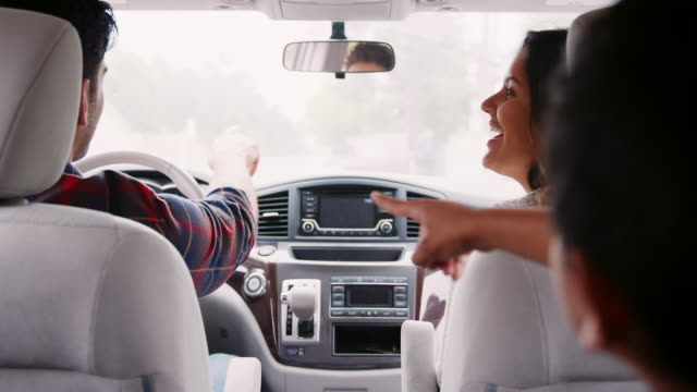 dad and his son pointing while driving in car with mum - viaggio in macchina video stock e b–roll