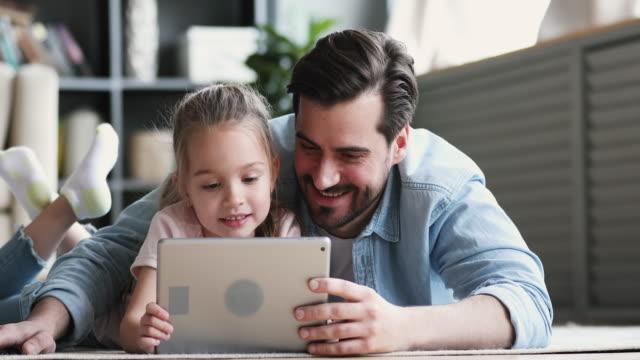 papà e la piccola figlia con tablet digitale sdraiati sul pavimento - industria elettronica video stock e b–roll