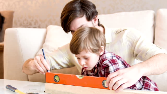 Dad and son are measuring together video