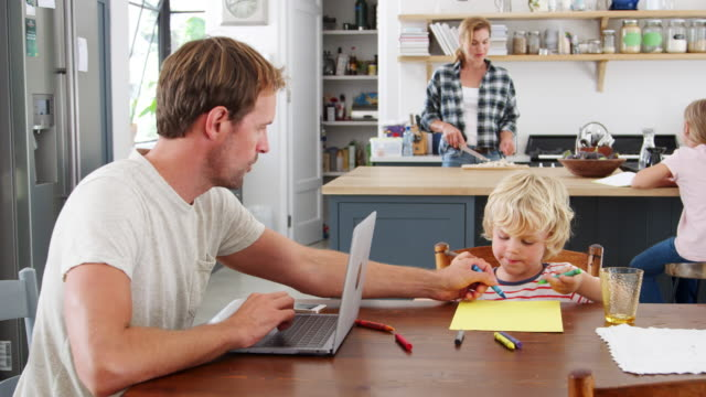 dad and son at kitchen table, mum and daughter in background - work from home stock videos & royalty-free footage