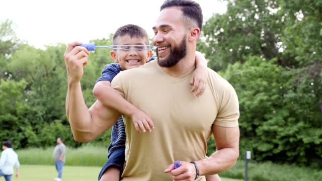 dad and son blowing bubbles in the park - picnic video stock e b–roll