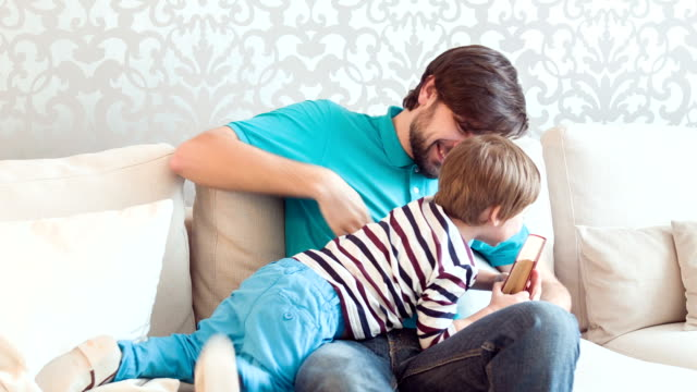 Dad and son in living-room Give it to me. Laughing dad and his little son sitting on white couch in living-room and wrestling for their favorite book wrestling stock videos & royalty-free footage