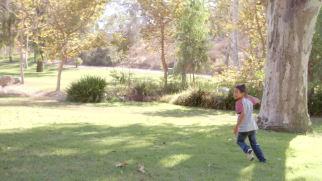 Dad and son passing American football to each other in park video
