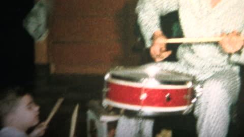 vidéos et rushes de (vintage 8 mm) 1965 père et fils jouant du tambour ensemble pour noël le matin - vintage