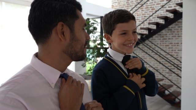 vídeos y material grabado en eventos de stock de papá e hijo hablando mientras papá le enseña a hacer su corbata sonriendo - corbata