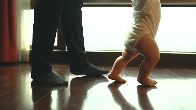Dad and son walking, Father helps a child to make baby steps evening in their home. Father playing with his baby after work. video