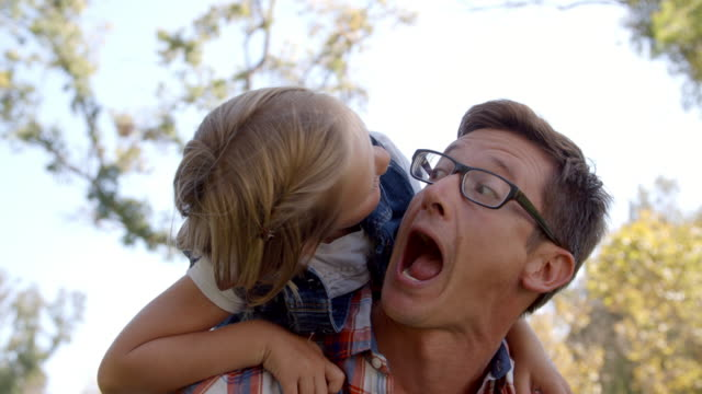 Dad and young daughter pulling faces in a park, front view