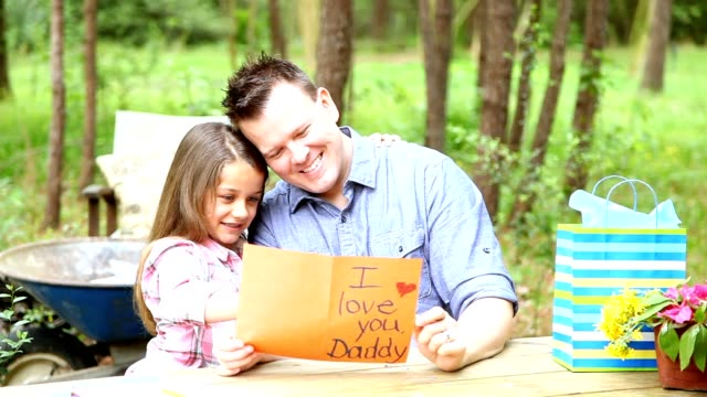 Dad, daughter outdoors with Father's Day or birthday gifts. video