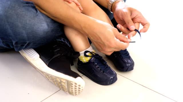 vídeos y material grabado en eventos de stock de papá ayudando a corbata zapatos mientras su hijo sentado en su regazo - amarrado