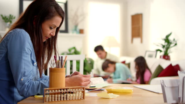 Dad helps girls with homework and mom does bills video