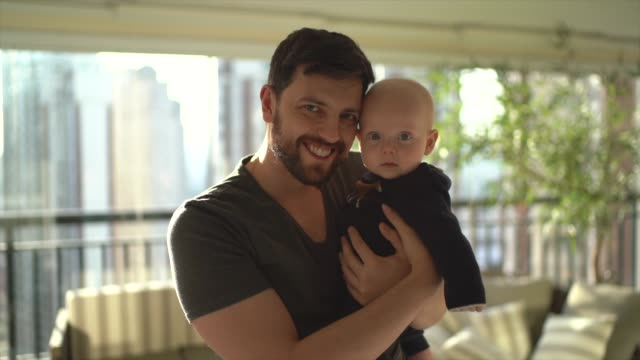 dad holding his son at home - 30 34 anni video stock e b–roll