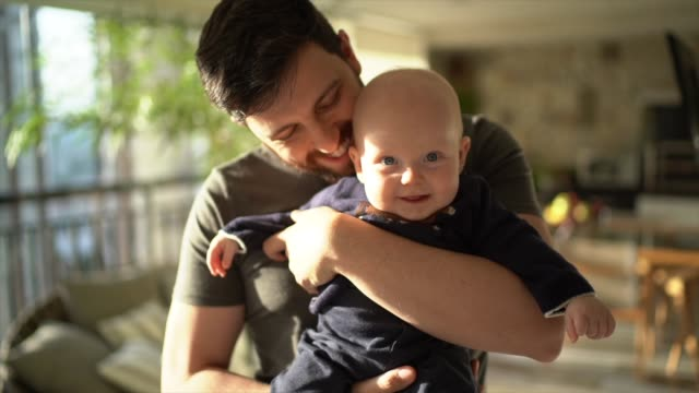 Dad holding his son at home