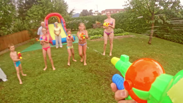 POV Dad in water gun fight with kids at a children's party video