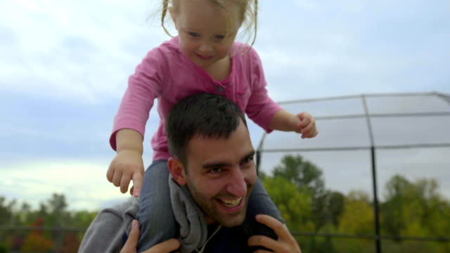 Dad jumps up an down with daughter on his shoulders video