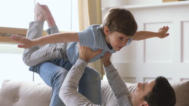 papà che solleva il figlio bambino gioca aereo divertendosi sul divano - figlio maschio video stock e b–roll