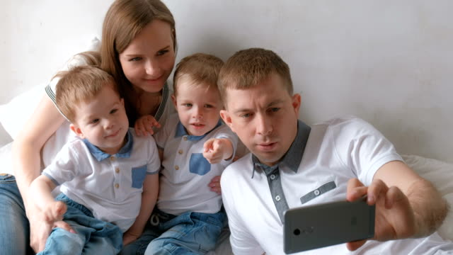 dad makes family selfie on mobile phone. mom, dad and two brother twins toddlers. - gemelle video stock e b–roll