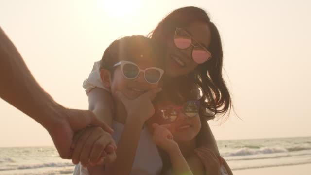 日没時に海の近くで一緒にリラックスしながら、自分撮りを取るためにカメラを使用してお父さん、お母さんと子供。4kスローモーション。 - 母娘 笑顔 日本人点の映像素材/bロール