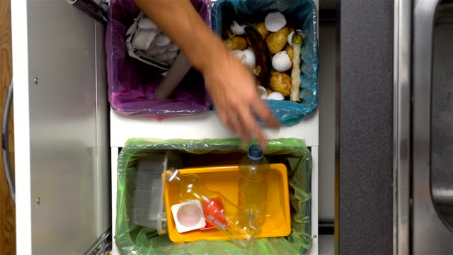 dad, mom and toddler recycling waste at home. close-up of hands. slow motion - odzyskiwanie i przetwarzanie surowców wtórnych filmów i materiałów b-roll