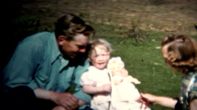 (8mm Vintage) 1952 Dad Mom & Baby Farm Picnic, Chickens In Background. Iowa, USA.