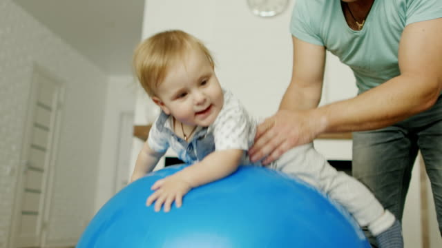 Dad plays with his young son at home. They jump on a massage ball video