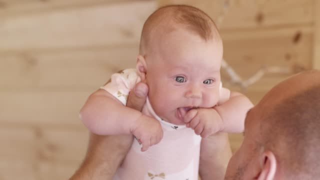 Dad plays with newborn daughter