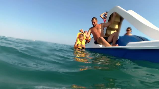 Dad pulls his son out of the sea into the catamaran video