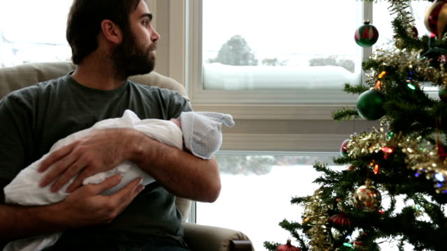 Dad rocking his newborn close to Christmas tree and Snowstorm DSLR video of a father rocking his baby boy newborn.  There is a nice Snowstorm in background. The video is panning from left to right. rocking chair stock videos & royalty-free footage