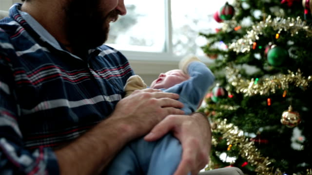 Dad rocking his newborn close to Christmas tree and Snowstorm DSLR video of a father rocking and feeding his baby boy newborn.  There is a nice Snowstorm in background. The video is panning from left to right. rocking chair stock videos & royalty-free footage
