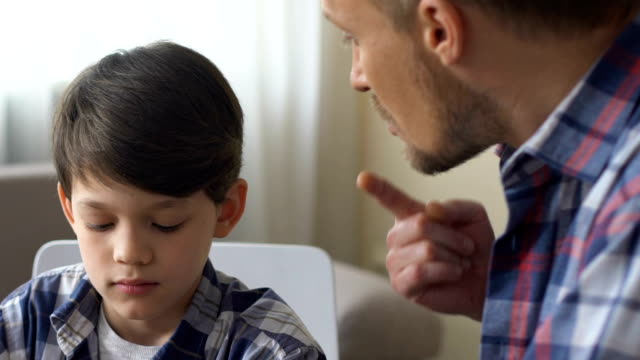 Dad scolds his son for bad behavior, discusses child discipline, remains calm Dad scolds his son for bad behavior, discusses child discipline, remains calm obedience stock videos & royalty-free footage
