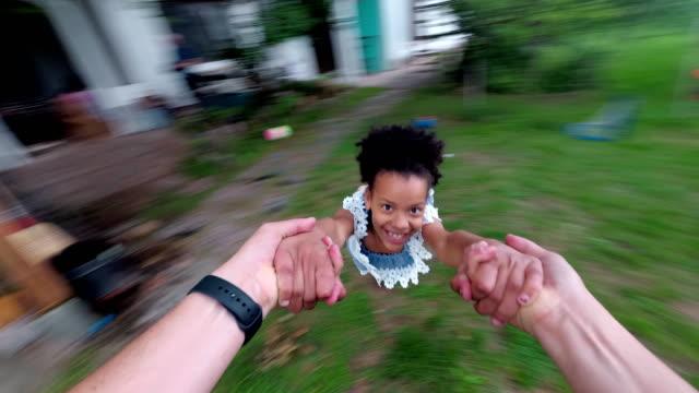 papà che gira bambina in aria - roteare video stock e b–roll