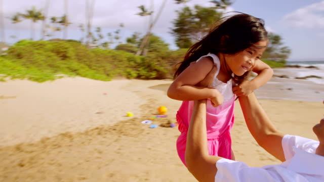 Dad spins daughter around at the beach video