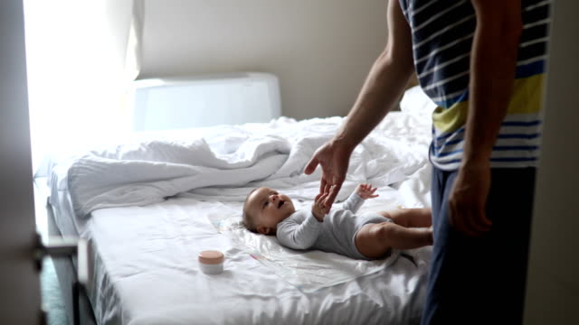 Dad taking dirty diaper out of the room - video