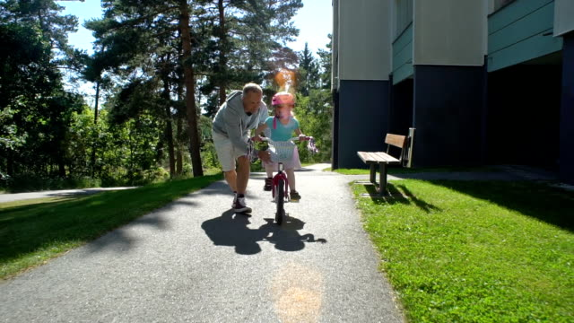 dad teaches his daughter to ride a bike - rower filmów i materiałów b-roll