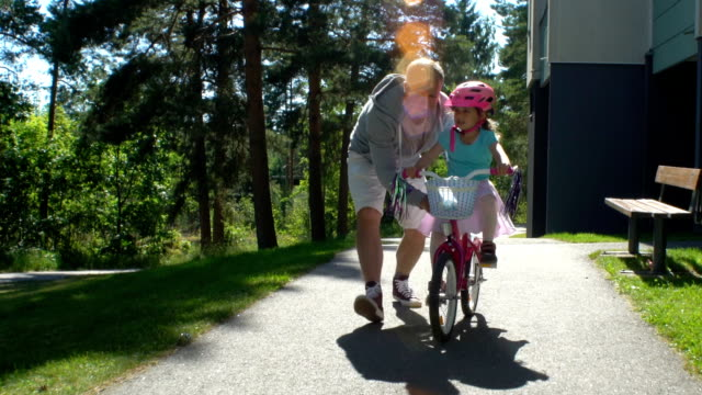 Dad Teaches his Daughter to Ride a Bike First cycling. Dad teaches his daughter to ride a bike. Slow Motion. teaching stock videos & royalty-free footage