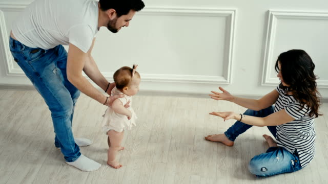 Dad teaches his little daughter to walk. Baby's first steps video