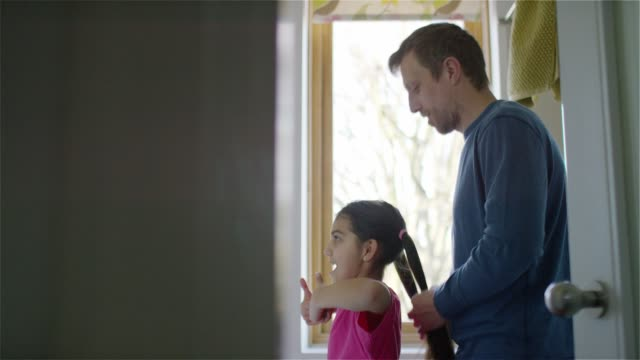 A dad ties his daughter's hair in a pony tail
