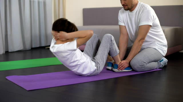 Dad training male kid to do crunches at home, active leisure, healthy lifestyle video