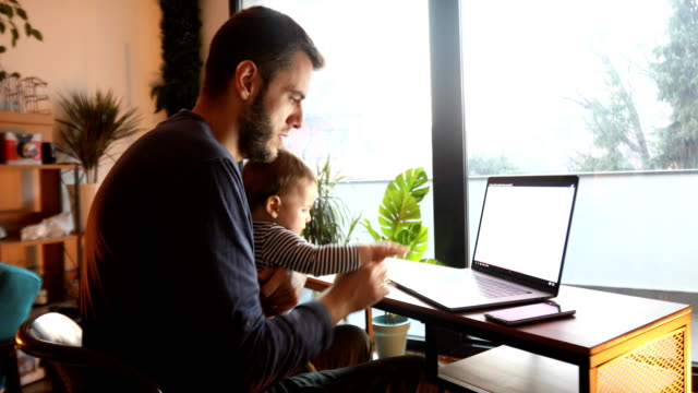 dad using laptop and holding his baby son - serbia video stock e b–roll