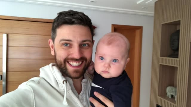 Dad with his newborn son doing a video call at home video