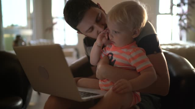 Dad working at home while stay with his son Dad working at home while stay with his son financial planning stock videos & royalty-free footage