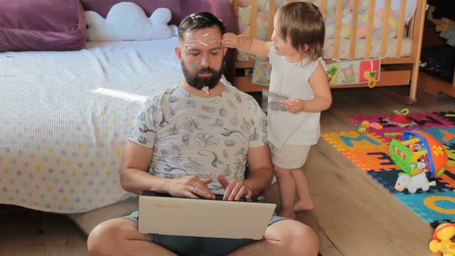 Dad working from home. His little daughter sticks shiny stickers on his face. Home quarantine self-isolation.